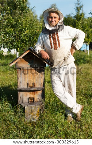 Happy beekeeper in protective hat and white shirt, is standing near the wooden beehive in the bee-garden with multicolor wooden beehives on the background, close up - stock photo