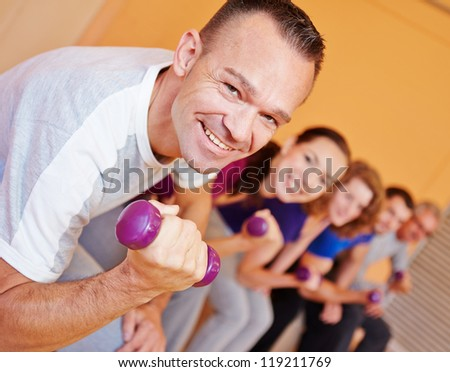 Happy best ager man in fitness center lifting dumbbells - stock photo