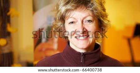 Happy best ager woman smiling in a gym - stock photo