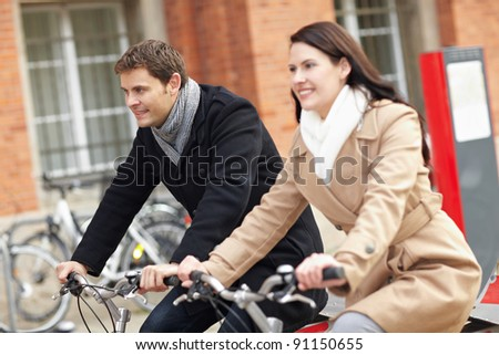 Happy bicyclists riding bikes in a city - stock photo