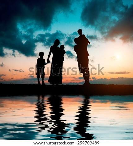 happy big family on a background of the magnificent sunset over the sea - stock photo