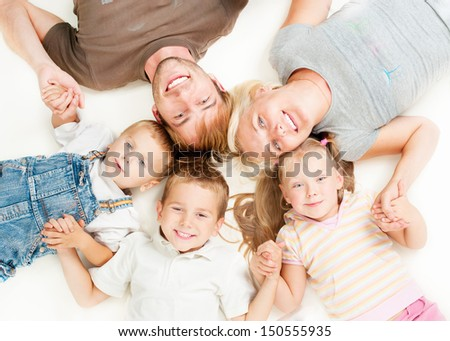 Happy Big Family Portrait. Father, Mother, Daughter and Sons Together Lying on floor and Holding Hands on White Background. Smiling Parents with Little Kids. Studio Shot - stock photo