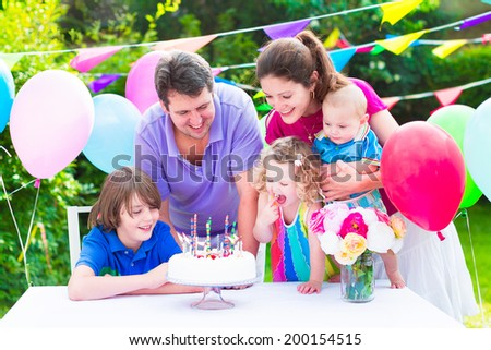 Happy big family with three kids - school age boy, toddler girl and a little baby enjoying birthday party with a cake blowing candles in a summer garden decorated with balloons and banners - stock photo