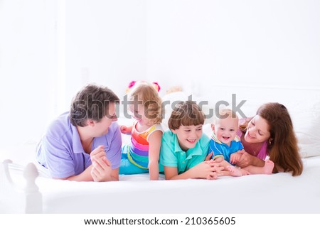 Happy big family, young parents with three kids, laughing boy, cute toddler girl and adorable little baby wearing colorful pajamas reading in bed in a white sunny bedroom at home - stock photo