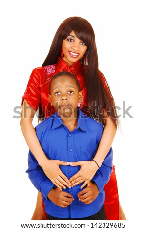 Happy big sister in a red dress holding her little brother in front of her, smiling with her long brunette hair for white background.  - stock photo
