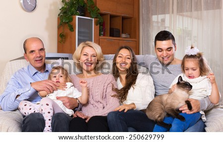 Happy big united family members laughing together in living room