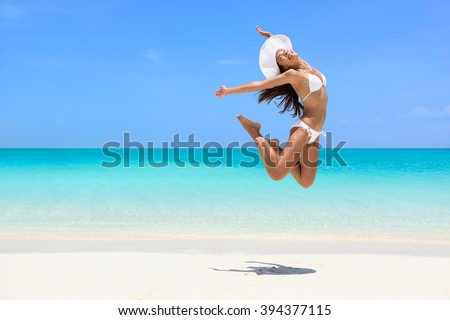Happy bikini woman jumping of joy on beach. Excited holiday girl doing a jump of freedom and happiness in a free body. Weight loss success healthy lifestyle concept. - stock photo