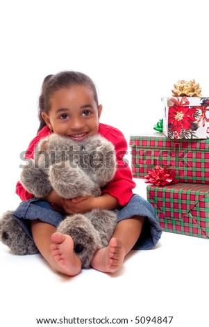 Happy biracial girl hugging a plush Christmas puppy with other wrapped gifts behind her.  Isolated on white. - stock photo