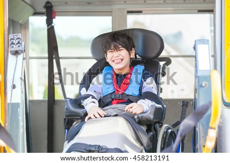 Happy biracial little boy with special needs sitting in wheelchair, riding on yellow school bus lift, going to school - stock photo