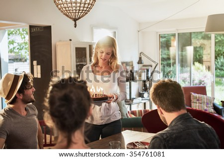 Happy birthday ! A nice blonde girl in her 30s is bringing the cake with lighted candles, to her friends. They are sitting at a wooden table in a charming house. They are wearing trendy casual clothes - stock photo