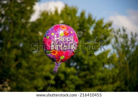 Happy birthday Balloons flying outdoors - stock photo