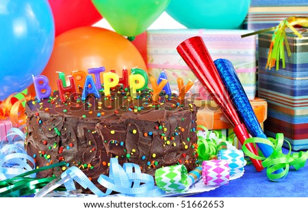 Happy Birthday candles on top of a chocolate birthday cake.  Colorful balloons, party horns and gifts surround the pretty cake. - stock photo