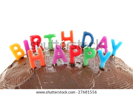 Happy Birthday candles on top of a chocolate cake with a white background. - stock photo