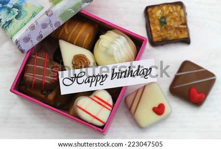 Happy birthday card with box of assorted chocolates  - stock photo