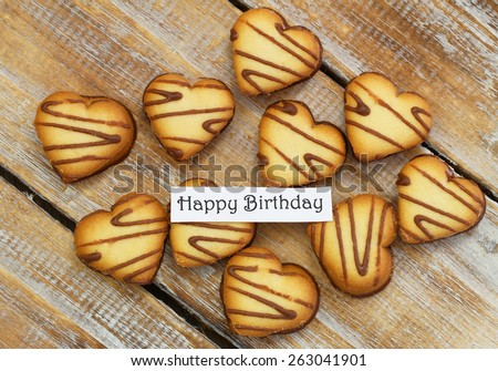 Happy birthday card with heart shaped cookies on rustic wood  - stock photo