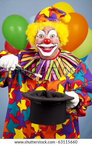 Happy birthday clown does a magic trick with a top hat and wand. - stock photo