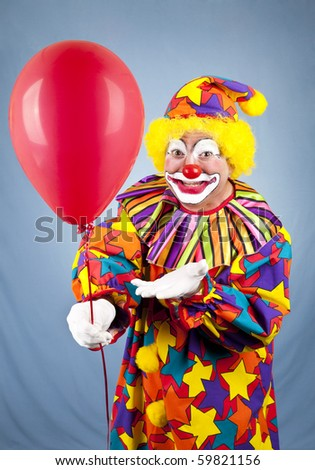 Happy birthday clown holding out a red balloon for you. - stock photo