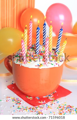 Happy birthday cup cake with lit candles and balloons.
