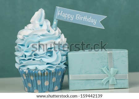 Happy birthday cupcake with present in baby blue - stock photo