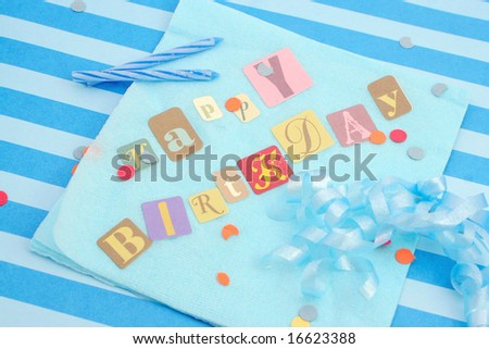 Happy birthday cut out letters on blue napkin with ribbons, candles, and  confetti