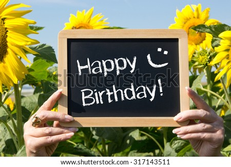Happy Birthday - female hands holding chalkboard with text and smiley, sunflowers in the background - stock photo