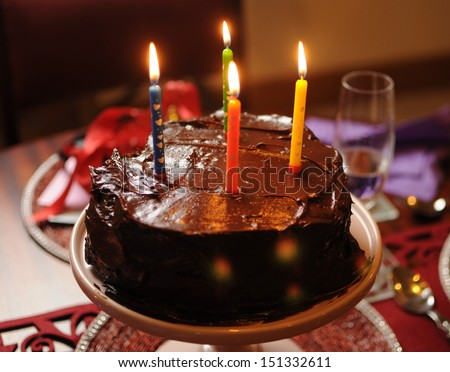 Happy birthday heart shape chocolate mud cake with four lit birthday candles on party party table setting. - stock photo