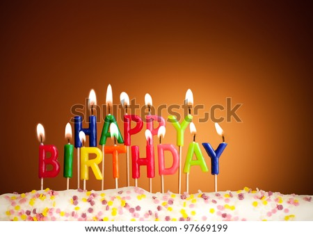 Happy birthday lit candles on brown background - stock photo