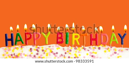 Happy birthday lit candles on orange background - stock photo