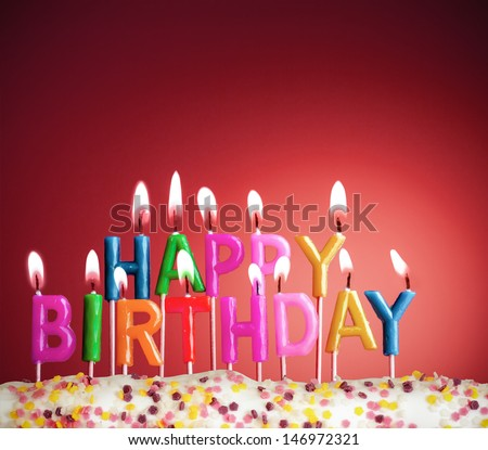 Happy birthday lit candles on red background - stock photo