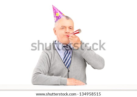 Happy birthday mature man with party hat blowing isolated against white background - stock photo