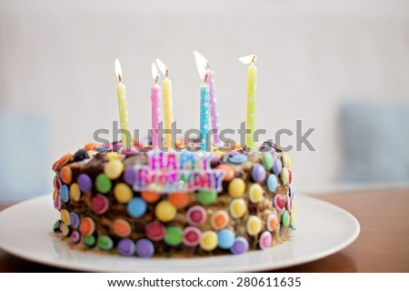 Happy Birthday sign and candles on child chocolate candy cake