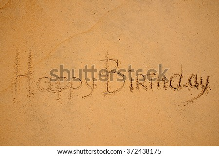 happy birthday sign written on the beach - stock photo