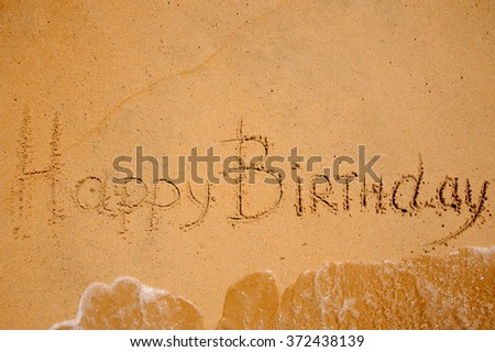 happy birthday sign written on the beach washed by wave  - stock photo