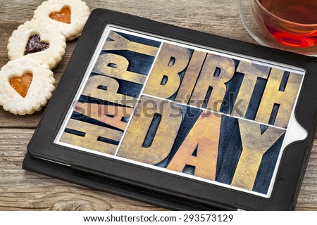 happy birthday typography - isolated text abstract in letterpress wood type printing blocks on a digital tablet with tea and heart cookies - stock photo