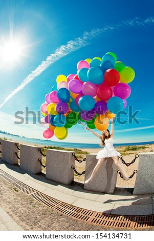 Happy birthday woman against the sky with rainbow-colored air balloons in hands. sunny and positive energy of urban street. Young beautiful girl on the grass in the city. - stock photo
