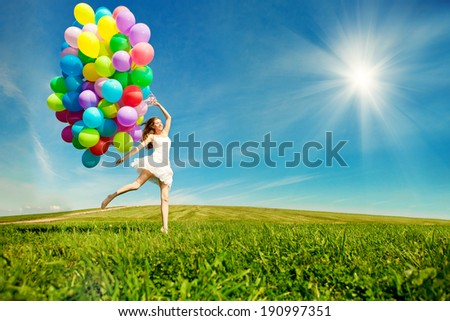 Happy birthday woman against the sky with rainbow-colored air balloons in hands. sunny and positive energy of nature. Young beautiful girl on the grass in the park. - stock photo