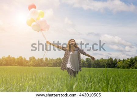 Happy birthday woman against the sky with rainbow-colored air balloons in hands. sunny and positive energy of nature. Young beautiful girl on the meadow in the park. - stock photo
