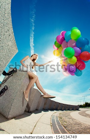 Happy birthday woman against the sky with rainbow-colored air balloons in her hands. sunny and positive energy of urban street. Young beautiful girl on the grass in the city. - stock photo