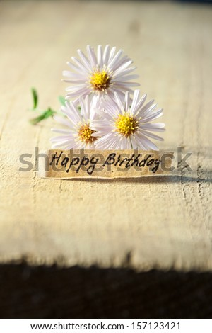 Happy birthday written on a banner, flowery background. - stock photo