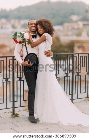 Happy black bride and groom softly hugging on the terrace with cityscape on background - stock photo