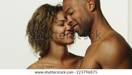 Happy black couple kissing and laughing - stock photo