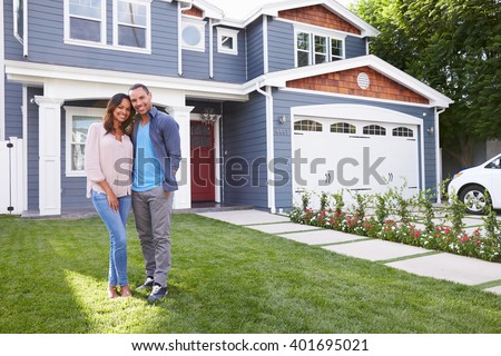 Happy black couple standing outside their house - stock photo