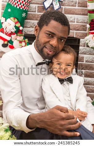 Happy black father and baby boy cuddling by fireplace. Christmas and New Year - stock photo