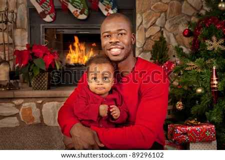 Happy Black Father and Son in front of Fireplace Decorated with Christmas Tree - stock photo