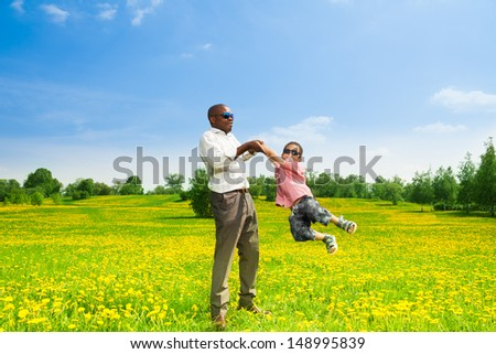 Happy black father with his son rotating his boy on the field with yellow dandelions in the park - stock photo