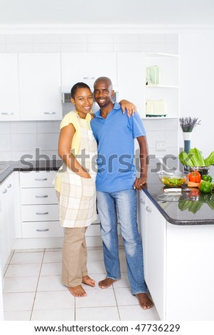 happy black husband and wife in kitchen - stock photo