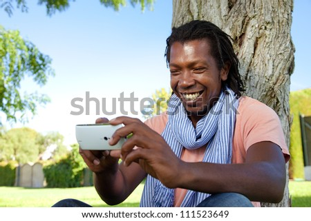 Happy black Jamaican man smiling using an smart phone in the park.