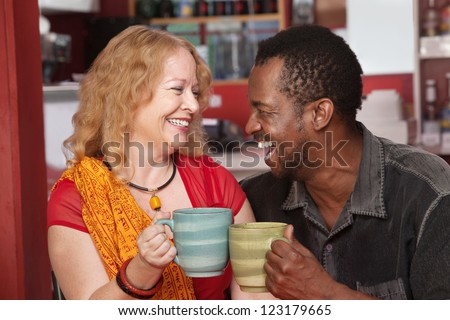 Happy Black man and European woman laughing together in cafe - stock photo