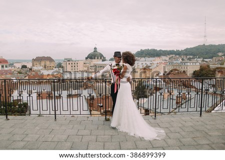 Happy black wedding couple softly hugging on the rooftop - stock photo
