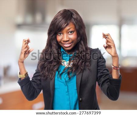 happy black-woman crossing fingers - stock photo